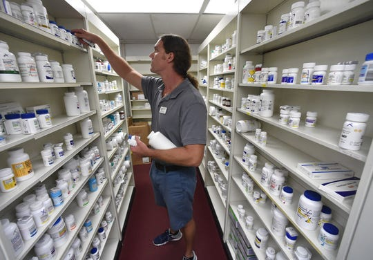 """Luke Fallis, pharmacy tech at Osceola Pharmacy, stocks the shelves with incoming medications on Thursday, Oct. 18, 2018, in Vero Beach. Falls has worked at the store 20 years. """"Customers like it when they come in and you know their face, know their name,"""" he said. """"They feel a little more comfortable."""""""