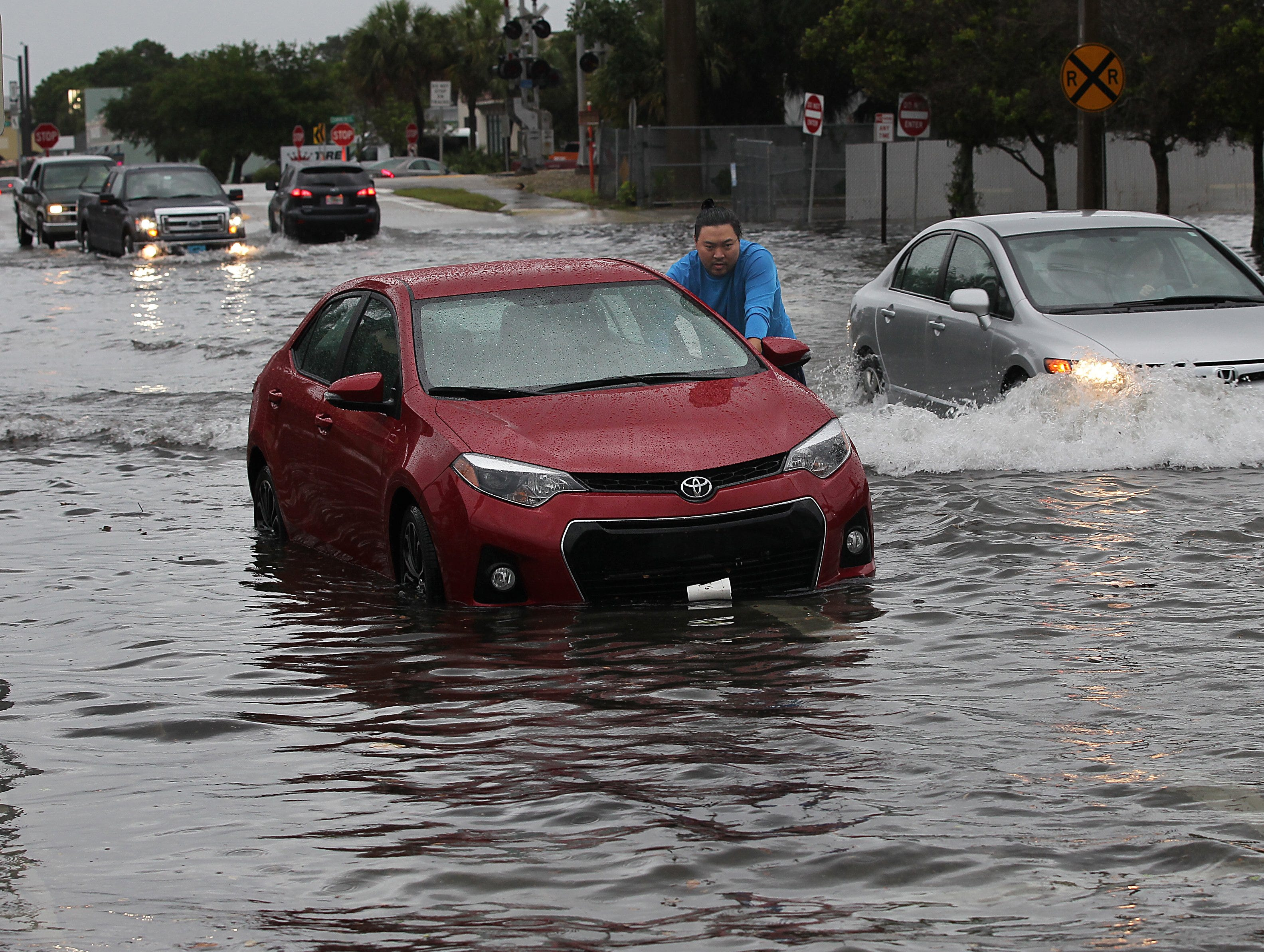 "John Yaung, of Grumpy's Burgers N Beer, a restaurant in Downtown Vero Beach, pushes a coworker's car to higher ground from a parking spot along 21st Street near 14th Avenue after being parked in water almost up to the tops of the tires Tuesday from a heavy rain storm. ""Little disheartening,"" Yang said after rescuing his car parked near his coworker's. ""No one is hurt, that's the important thing.""  (ERIC HASERT/TREASURE COAST NEWSPAPERS) John Yaung, cq PHOTOGRAPHED: Tuesday MAY 17, 2016"