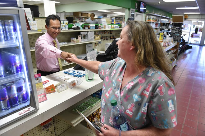 """Kazi Imam (left), registered pharmacist and owner of Osceola Pharmacy, greets customer Patricia Below, of Vero Beach, after she picked up a prescription for her husband and attended a seminar on medication management at Osceola Pharmacy on Thursday, Oct. 18, 2018, in Vero Beach. """"Oh, he's wonderful,"""" Below said. """"Every time I have a question he helps me."""" Imam, of Lake Worth, has owned  the pharmacy for about a year.  """"One of the reasons I drive here every day, about 180 miles, is that tradition. That pharmacy's been here for 100 years. That means there is something good in it,"""" Imam said."""
