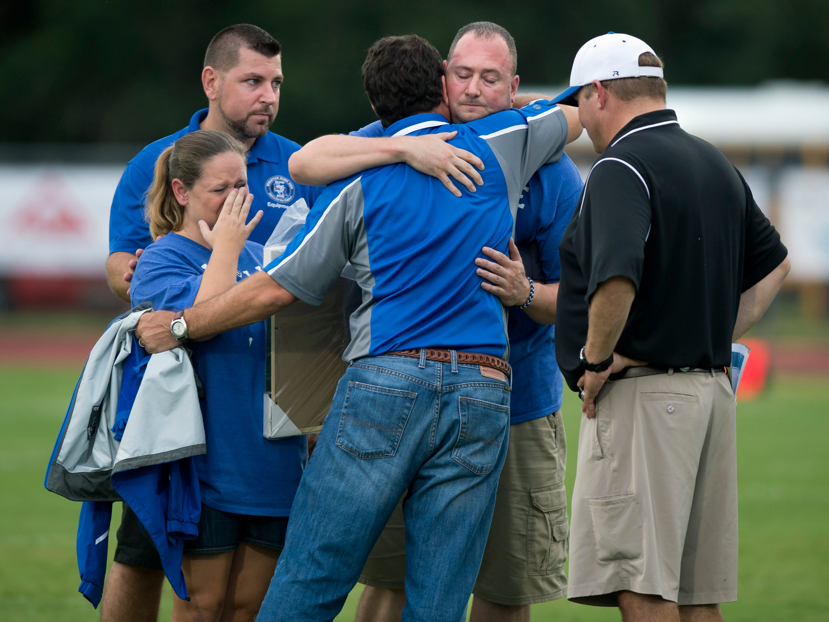 "William Shogran (second from right) receives a hug from Sebastian River High School principal Todd Racine (center) after Shogran and his wife Courtney were presented with a plaque and football prior to the start of the Sharks' game against Fort Pierce Westwood. The Showgrans' son, William Shogran, Jr., 14, died while practicing with the football team at Camp Blanding, a military base in Starke in north Florida, on August 13. ""We just wanted to show (the team) that we're here for them,"" said Courtney. Jim Adams, youth pastor at Sebastian Christian Church, stands at left and football coach Kevin Pettis stands at right. (SAM WOLFE/TREASURE COAST NEWSPAPERS)"