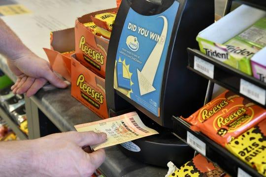 A customer checks his lottery ticket at 4 Seasons Handy Mart in Visalia on Wednesday, October 17, 2018.