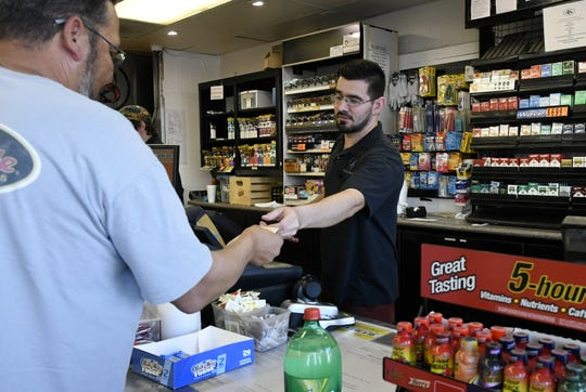 Employee Jerry Saavedra sells a lottery ticket for the California Lottery Mega Millions at 4 Seasons Handy Mart in Visalia on Wednesday, October 17, 2018.