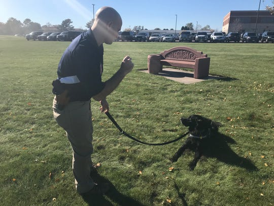 Wausau School Resource Officer Nick Stetzer works with his therapy dog, Badge, outside Barron schools on Thursday, Oct. 18. Stetzer and Badge visited with students and staff reeling from the disappearance of schoolmate Jayme Closs and the shooting deaths of her parents, James and Denise Closs.