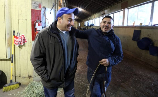 Ara Aprahamian of Bardonia, left, owner of racehorse Uncle Benny, jokes with assistant trainer Henry Argueta in Barn 50 at Belmont Park before a morning workout for the Breeders' Cup-bound thoroughbred.