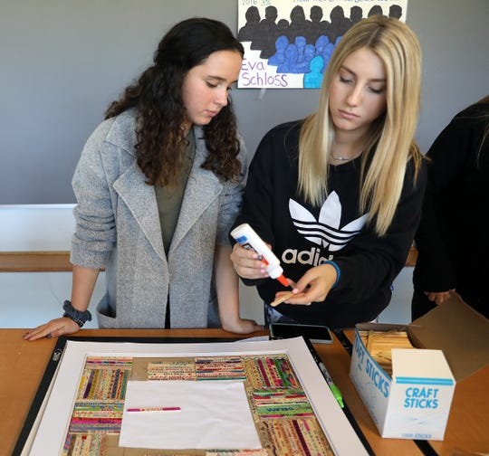 From left, Brooke Surgan and Samatha Bristow, both 17, glue Popsicle sticks with messages of encouragement on a picture frame Thursday for the school's guest speaker, Eva Schloss, a Holocaust survivor, at Suffern High School. Schloss, the stepsister of Anne Frank, will speak about her experience to the students on Monday.