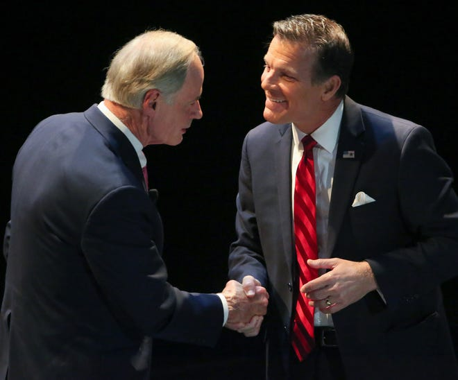 Incumbent Tom Carper (left) and Republican challenger Rob Arlett meet after a debate at the University of Delaware's Mitchell Hall. The two are vying for a US Senate seat.
