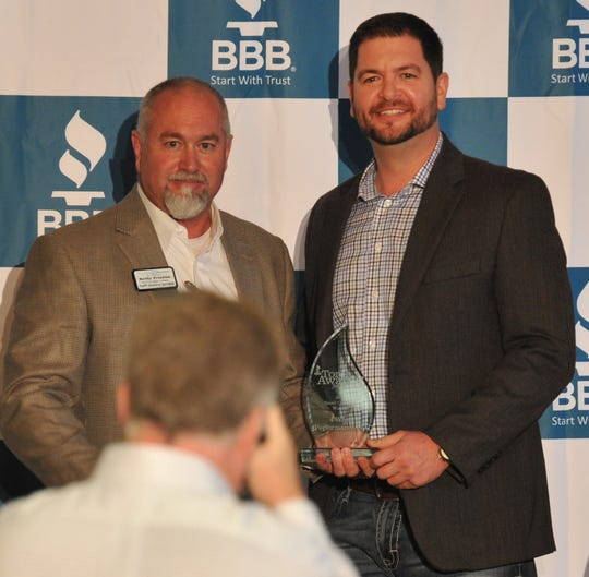 Dawson Druesedow, owner of 4 Wheel Performance, poses for pictures with presenter Kelly Fristoe, left, after being announced as the winner of the 2018 Better Business Bureau Torch Award for the small category.