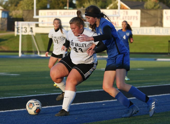 Tri-Valley's Kinzer Manning and Zanesville's Melena Moore battle for the ball.