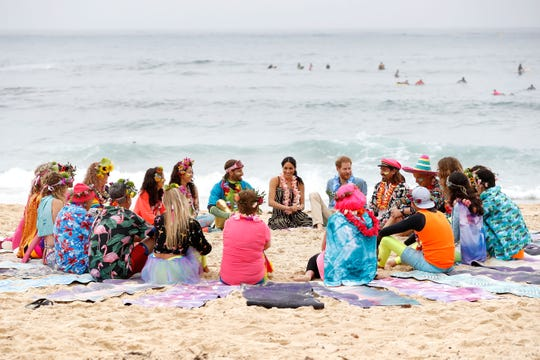 Prince Harry and Meghan, Duchess of Sussex, talk to members of OneWave, an awareness group for mental health and well-being at South Bondi Beach in Sydney.
