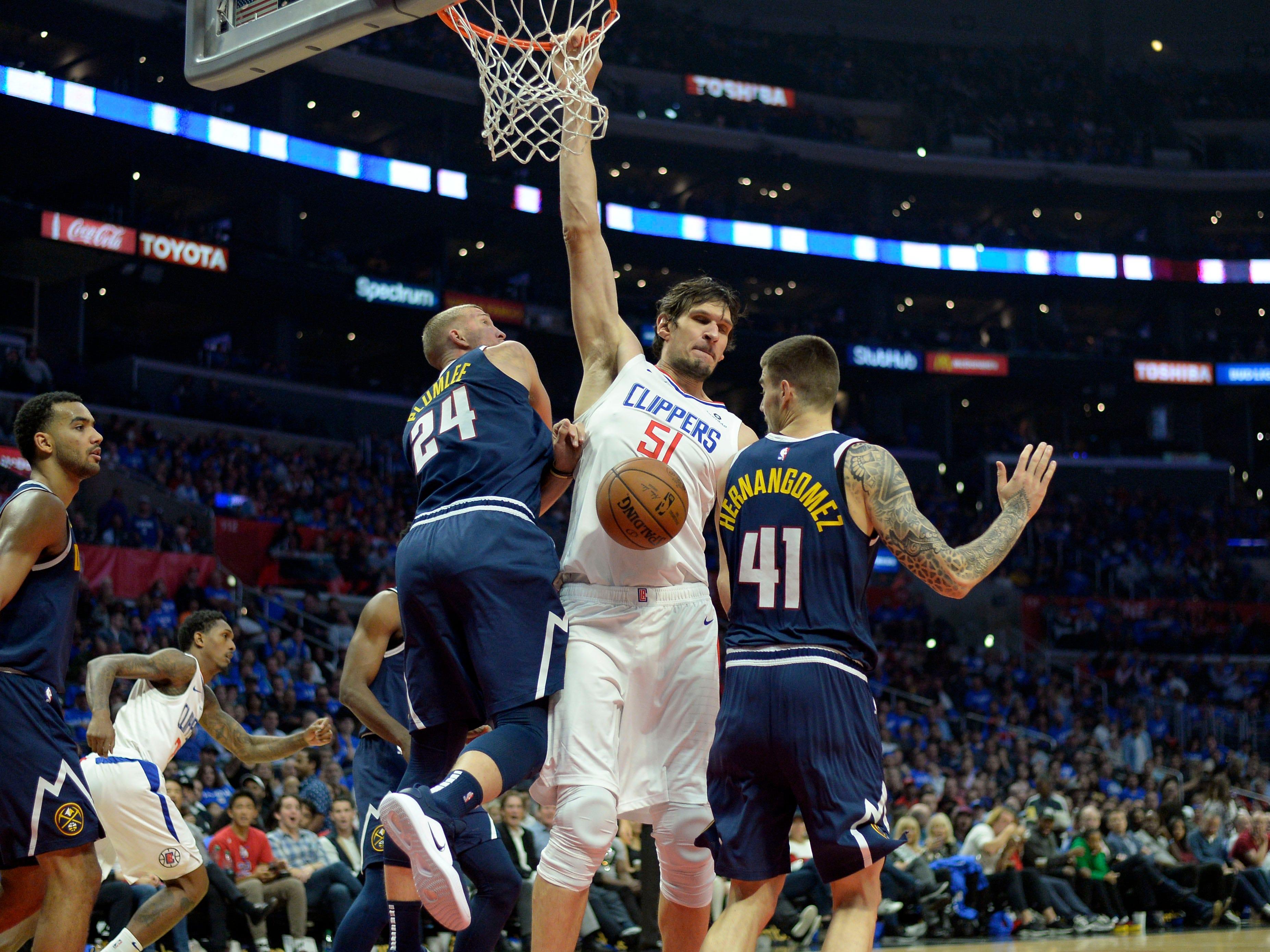 Oct. 17: LA Clippers center Boban Marjanovic dunks over Denver Nuggets forward Mason Plumlee and forward Juan Hernangomez during the fourth quarter at Staples Center.