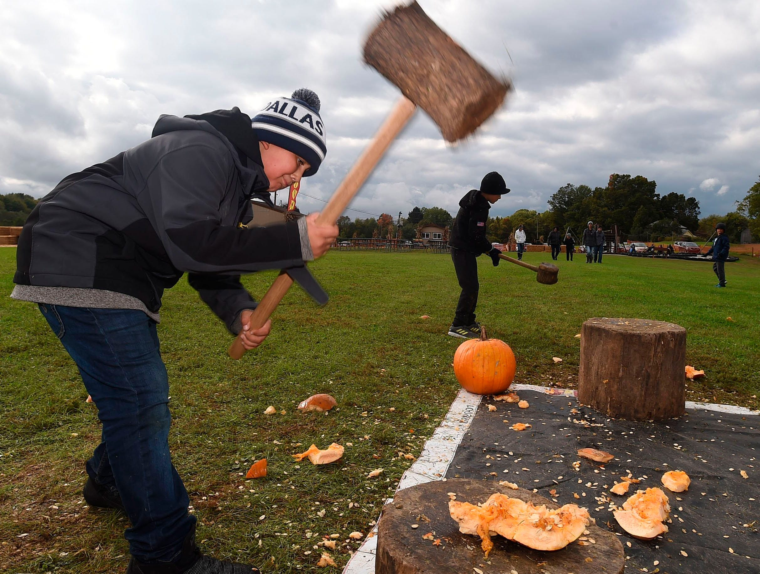 Zion Thomas, 10, of Ashtabula, Ohio, smashes pumpkins at Sissons Pumpkin Patch in Girard Township, Pa., Saturday, Oct. 13, 2018. (Jack Hanrahan/Erie Times-News via AP) ORG XMIT: PAERI601