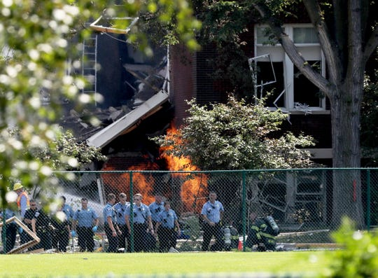 Emergency personnel move away as a gas fire burns after an explosion at Minnehaha Academy in Minneapolis Aug. 2, 2017.