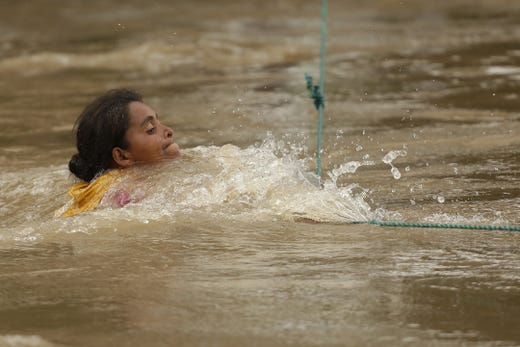 A woman, part of the group of Honduran migrants on the border of Honduras with El Salvador crosses the Goascoran River despite the increased flow caused by intense rains in the last hours, in El Amatillo, eastern Honduras, Oct. 18, 2018.