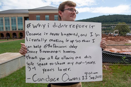 Luke Cromwell of Lynchburg, VA, holds a sign with a tweet from conservative commentator Candace Owens on the campus lawn of Liberty University. Owens was the school's convocation speaker on Sept. 26.