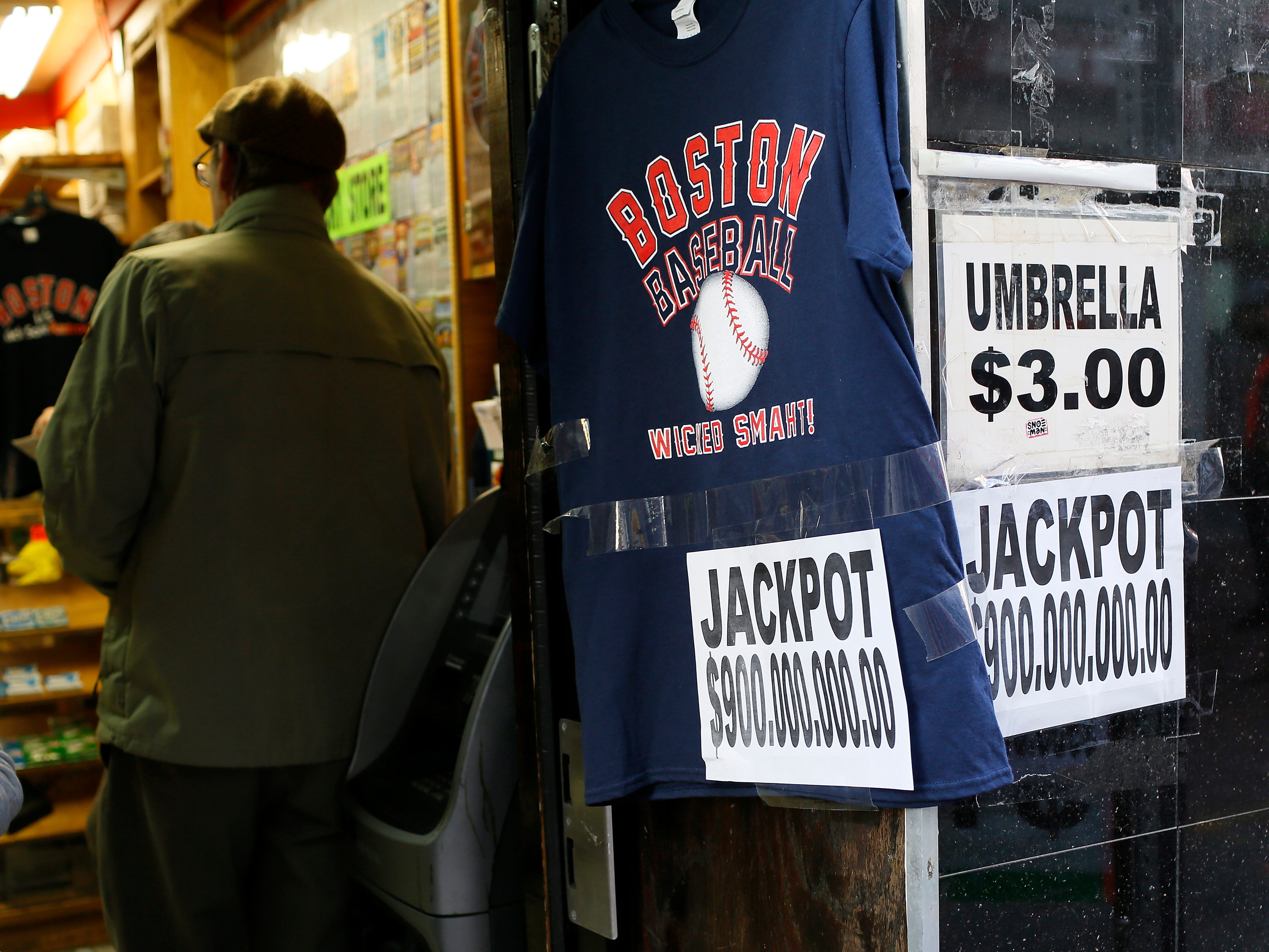 Signs are displayed outside a lottery sales booth in downtown Boston, Oct. 18, 2018.