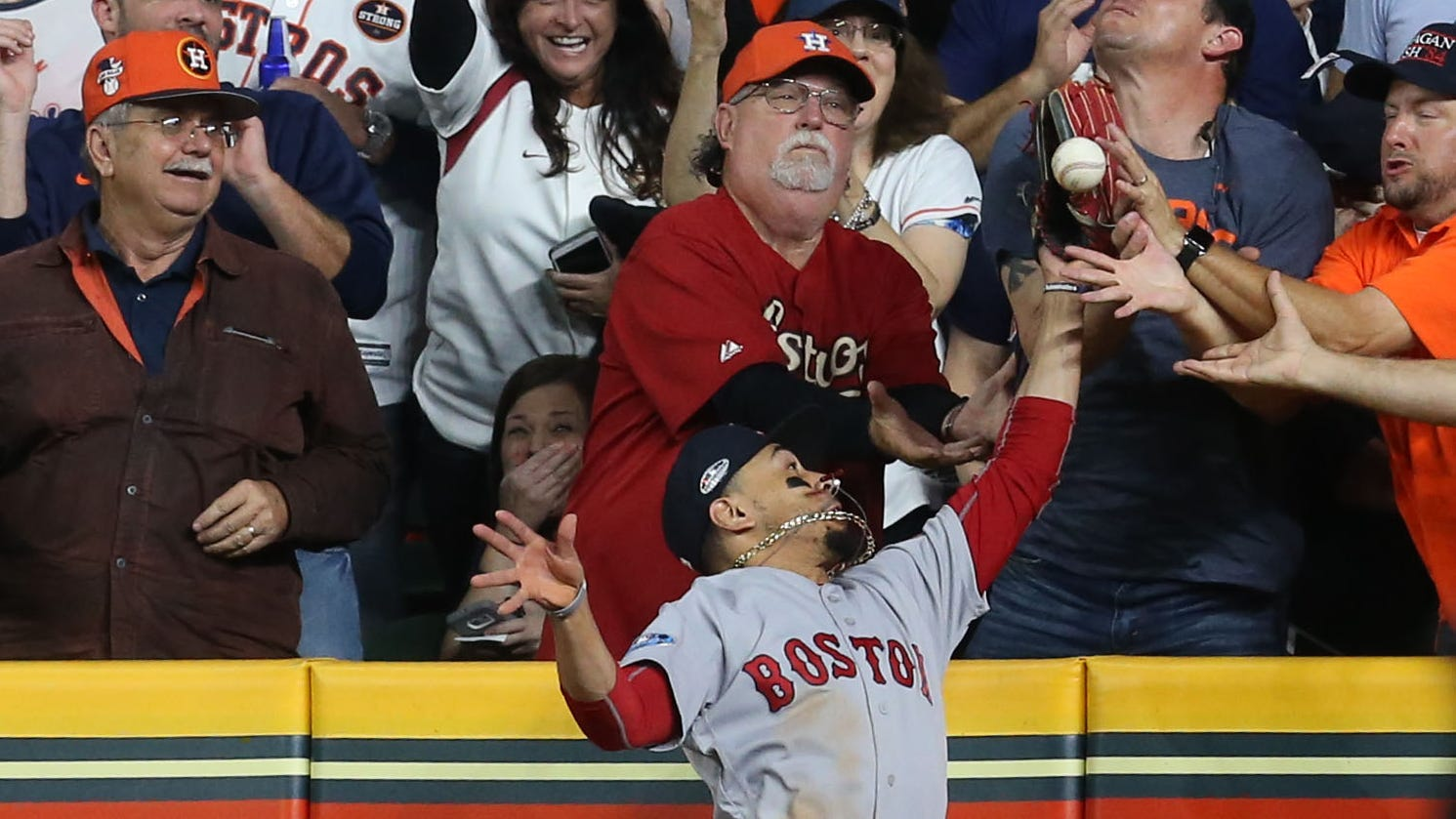 Red Sox right fielder Mookie Betts battles fans in the right field seats for a ball hit by the Astros' Jose Altuve. Umpires ruled the fans interfered with Betts and Altuve was called out.