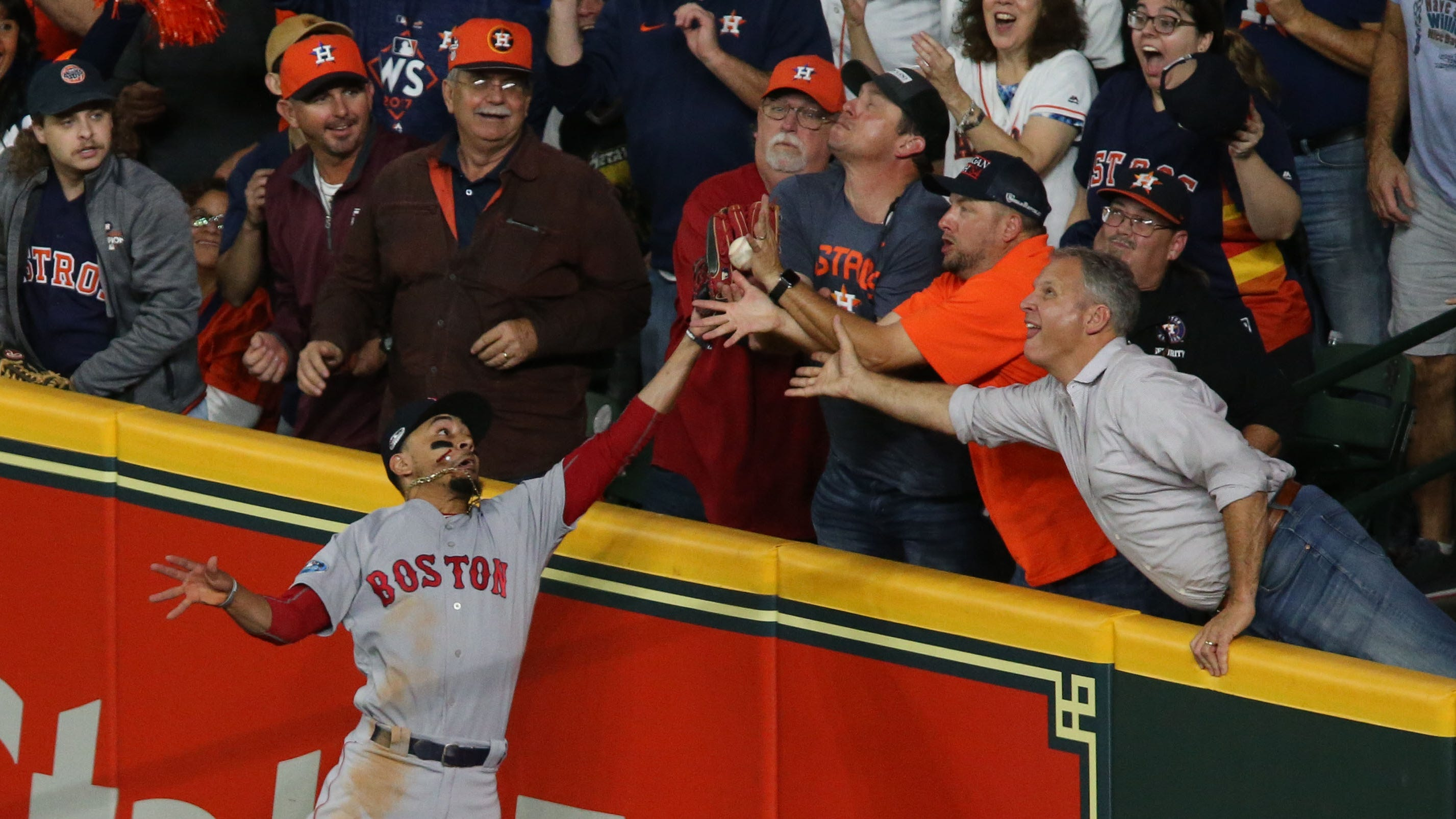 Red Sox right fielder Mookie Betts tries to catch a ball hit by Astros second basman Jose Altuve during the first inning of Game 4 of the ALCS. The play was ruled fan interference.