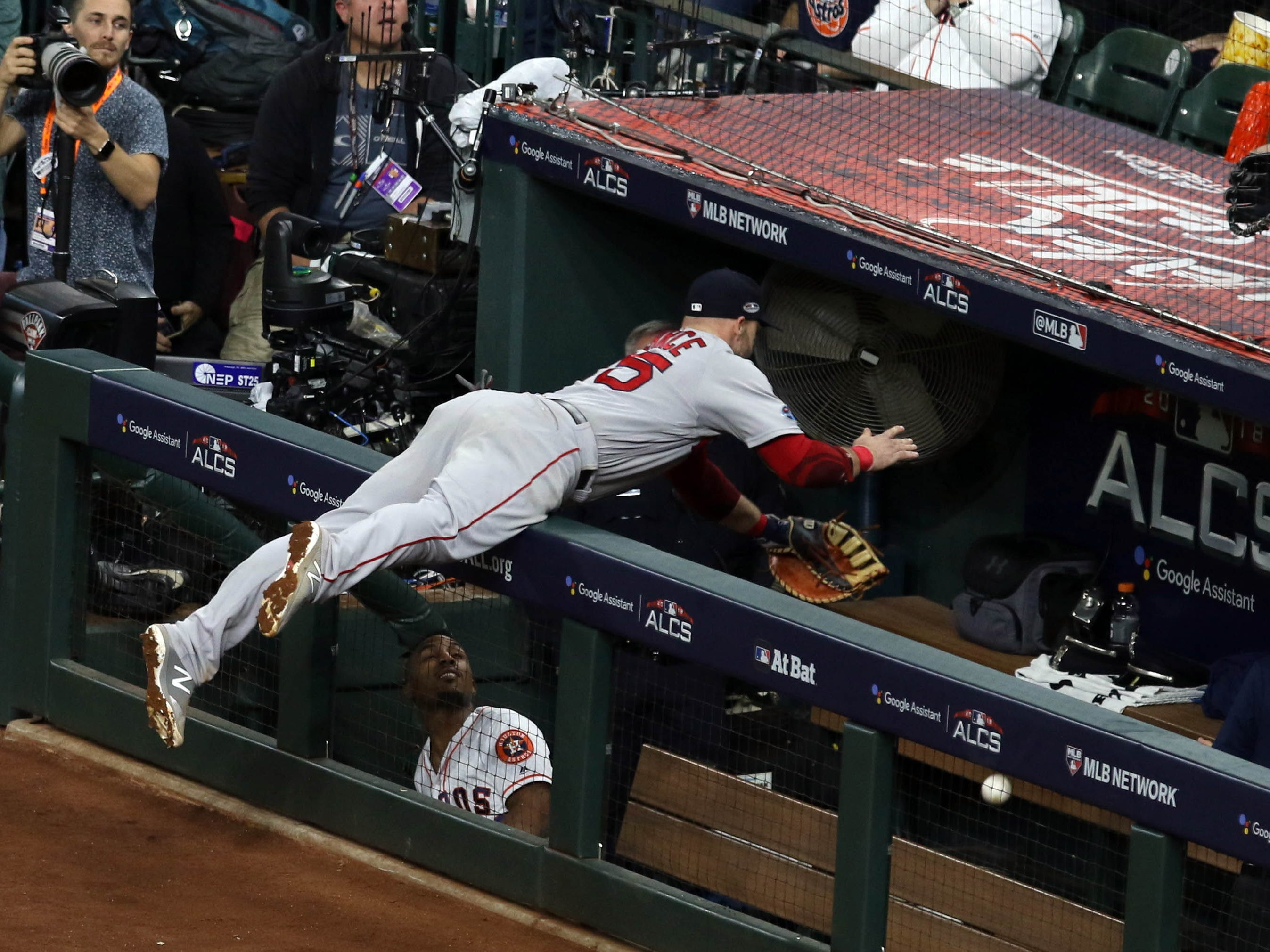 ALCS Game 4: Red Sox first baseman Steve Pearce attempts to make a catch and flips into the Astros dugout in the seventh inning.
