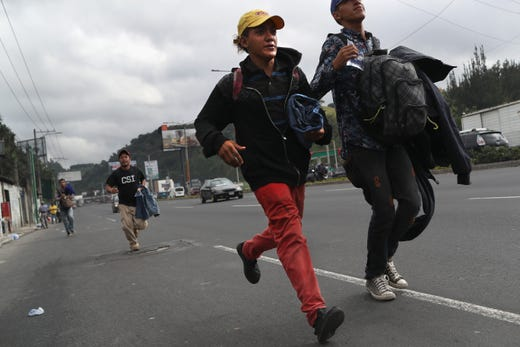 Migrants run to board a bus as part of a caravan of immigrants en route to the Mexican border in Guatemala City, Guatemala. Oct. 18, 2018.