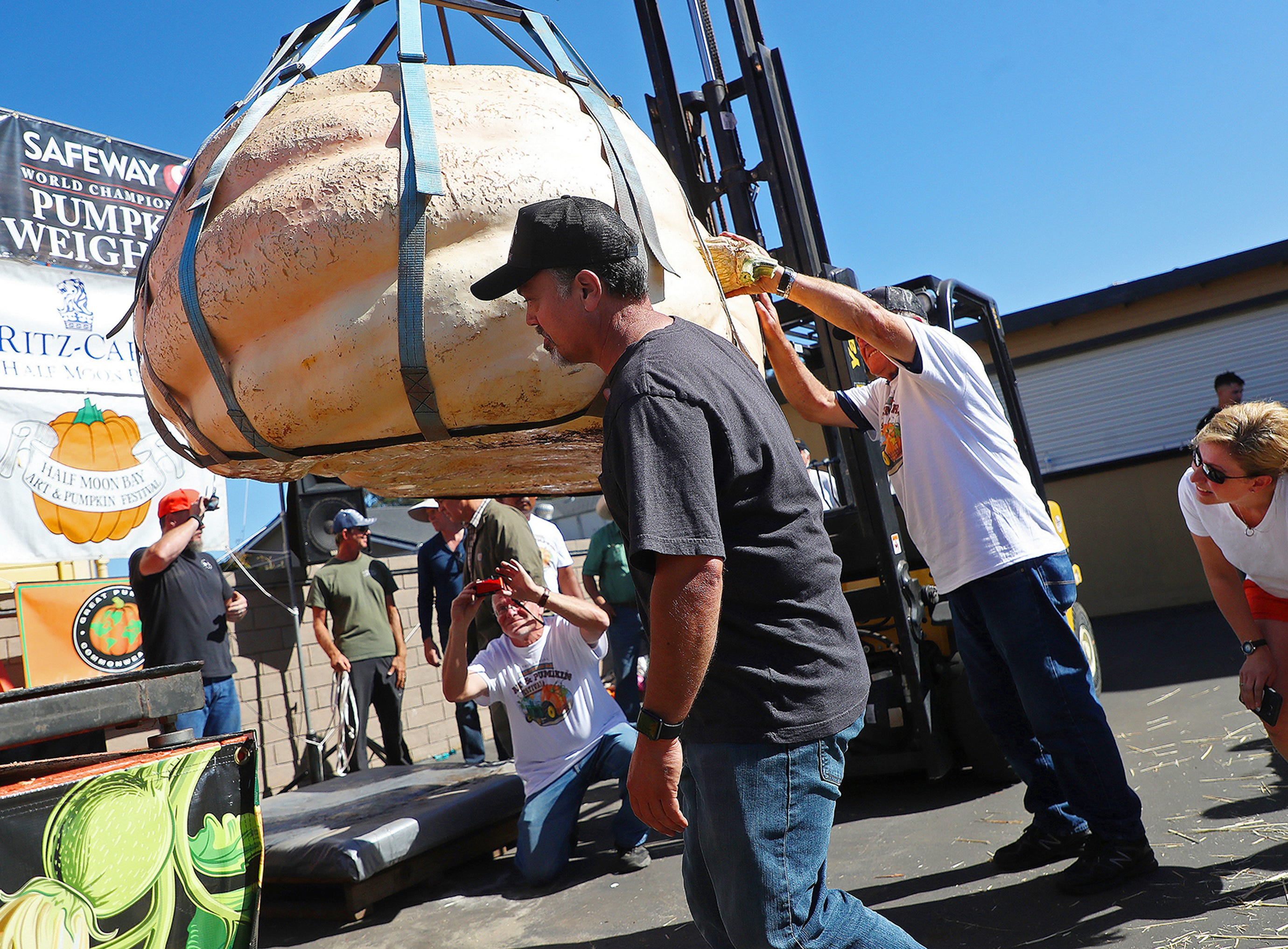 Judges inspect the first place pumpkin in the 45th annual Safeway World Championship Pumpkin Weigh-Off on Monday, Oct. 8, 2018, in Half Moon Bay, Calif. A commercial pilot from Oregon raised a giant pumpkin weighing 2,170 pounds (984 kilograms) to win a pumpkin-weighing contest in Northern California. Steve Daletas credited a good seed and lots of sunny days since he planted it April 15. It is the fourth time Daletas takes top honors at the annual pumpkin-weighing contest. (Aric Crabb/Bay Area News Group via AP) ORG XMIT: CAJOS503