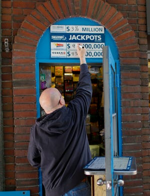 An attendant changes the signage for the Mega Millions jackpot total outside a lottery booth in downtown Boston, Massachusetts, on October 18, 2018. The estimated jackpot total for the drawing is $970,000,000.