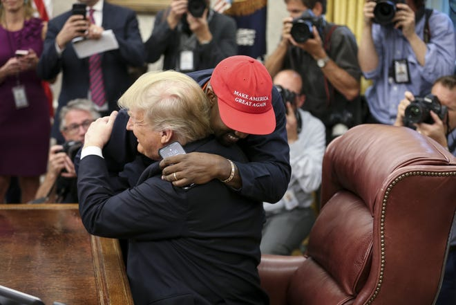 Kanye West hugs President Donald Trump during a meeting in the Oval Office.