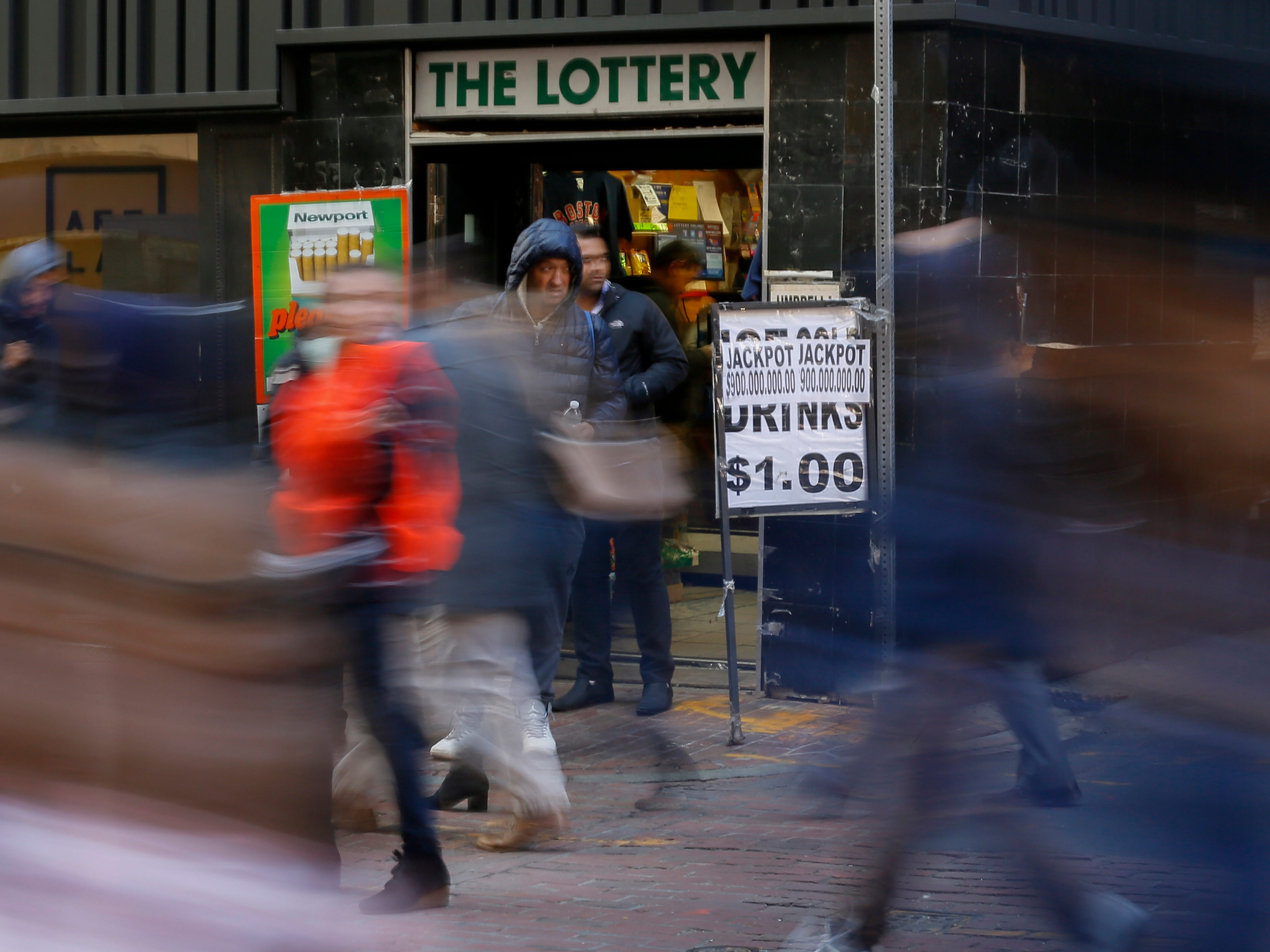 People walk past a lottery sales booth in downtown Boston, Oct. 18, 2018.