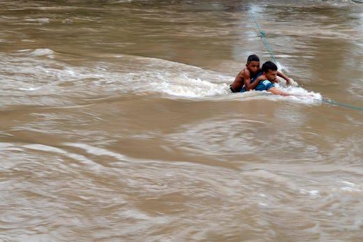 Honduran migrants attempt to cross the border Goascoran River to enter illegally to El Salvador, in Goascoran, Honduras Oct. 18, 2018.