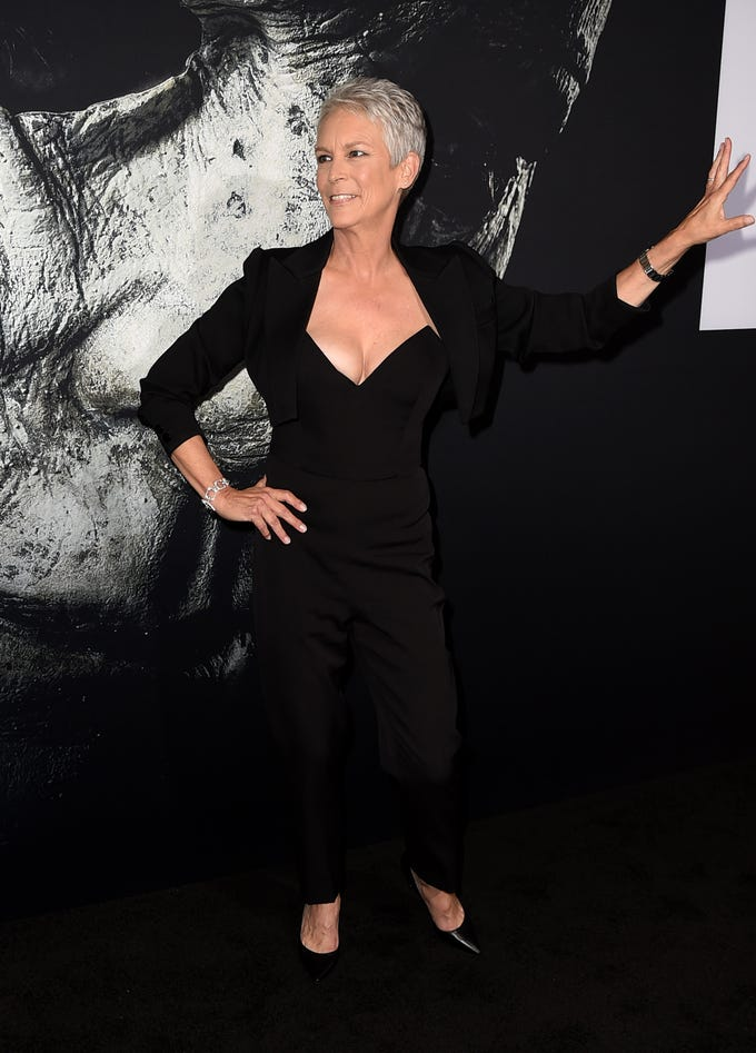 """Halloween"" is here! Jamie Lee Curtis looks glamorous, in front of a scary photo of the Michael Myers mask, at the Los Angeles premiere for her film."