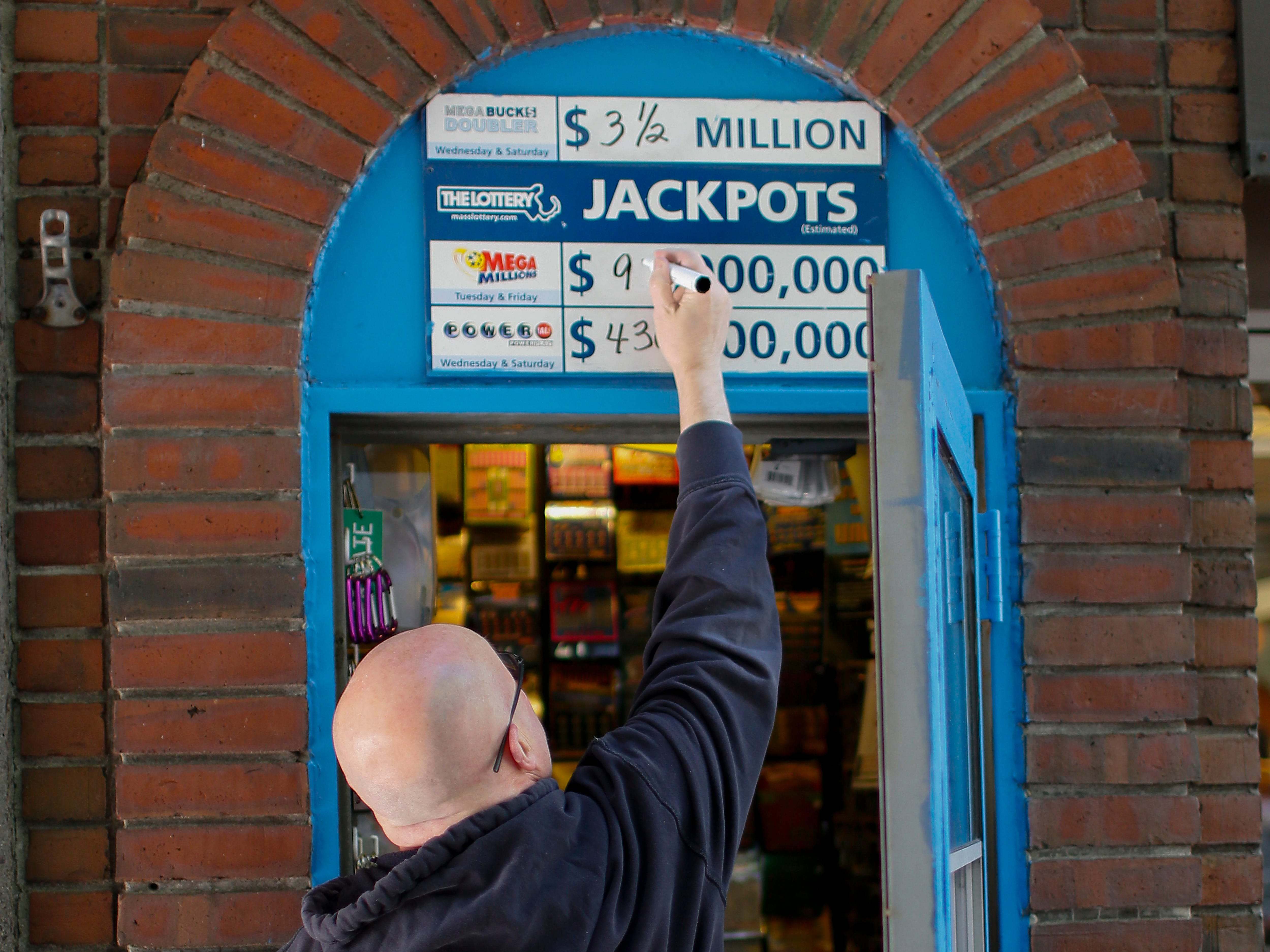 An attendant changes the signage for the Mega Millions jackpot total outside a lottery booth in downtown Boston, Oct. 18, 2018.