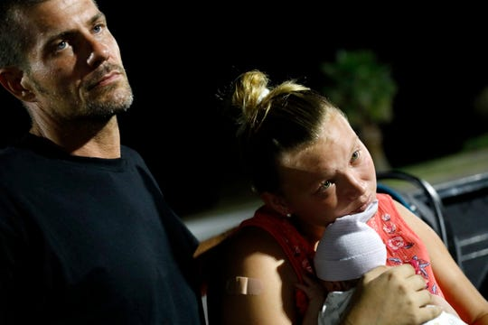 Lorrainda Smith, holding her 2-day-old son, Luke, and husband, Wilmer Capps, listen as police offer them an escort to a nearby hospital for assistance with a place to spend the night after the couple contemplated sleeping in their truck in a parking lot in Panama City, Fla., Monday, Oct. 15.