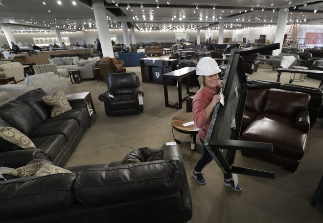 Assistant buyer Jenny Gagan sets up furniture vignettes at the new WG&R store  in Grand Chute.