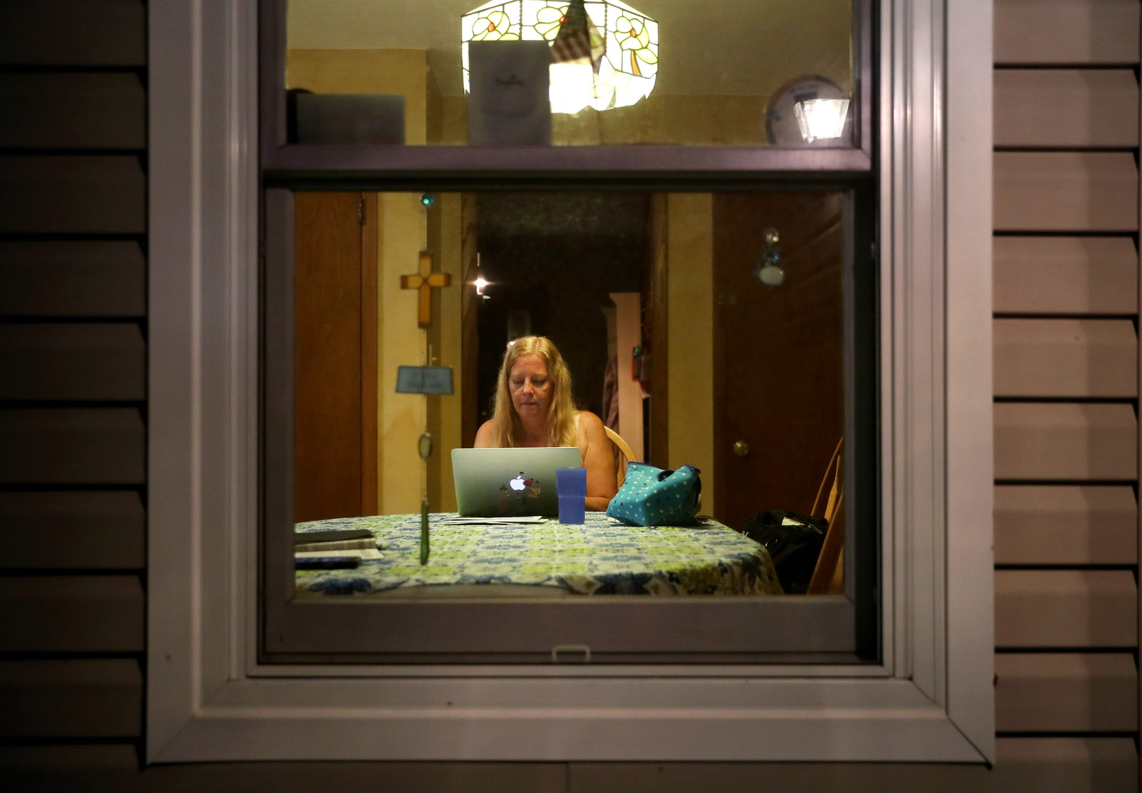 Maripat Franke, a special education teacher at Neenah High School currently enrolled in the Residency In Teacher Education 2.0 program at CESA 6, can be seen through her kitchen window checking emails after finishing her workday and teaching a baton twirling class at the Neenah/Menasha YMCA on  Sept. 17, 2018, in Neenah, Wis. Danny Damiani/USA TODAY NETWORK-Wisconsin