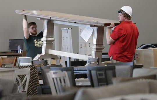 Employees Jeff Olson, left, and Patrick Umentum move a dining room table into place Thursday at the new WG&R store in Grand Chute.