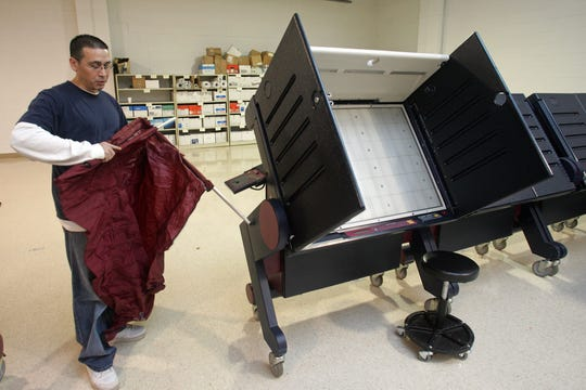 8828 Voting machine technician Michael VanPelt puts away a curtain to one of the voting machines at the Middlesex County Voting Machine Warehouse in Metuchen. Many of the machines have been shipped to voting sites already. Photo by Kathy Johnson 10/29/09