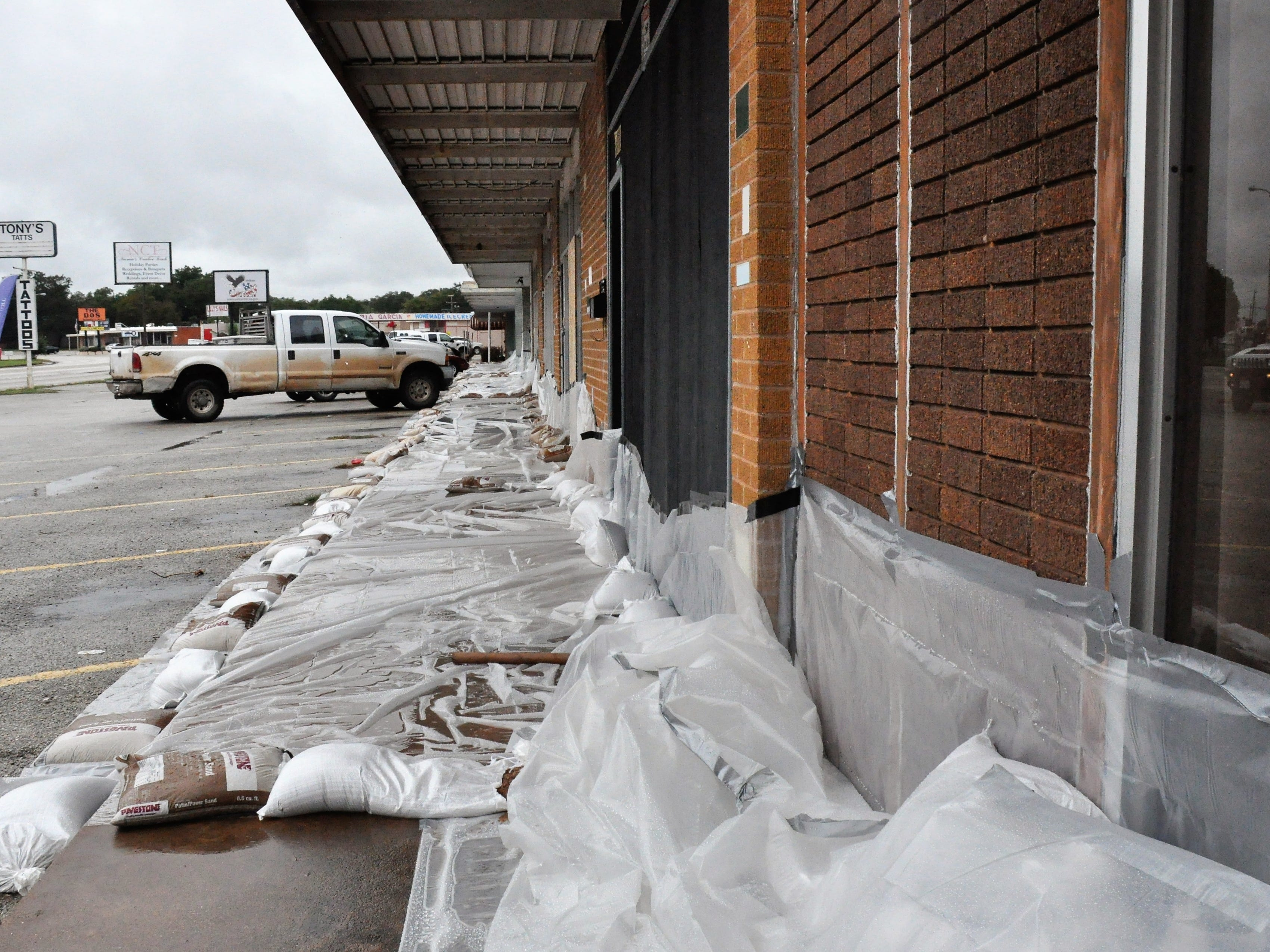 Several businesses at the Westwood Shopping Center at North Sixth and Willis streets are lined with plastic sheeting held down with sandbags to guard against flooding on Friday, Oct. 19, 2018, in case nearby Elm Creek overflows its banks.