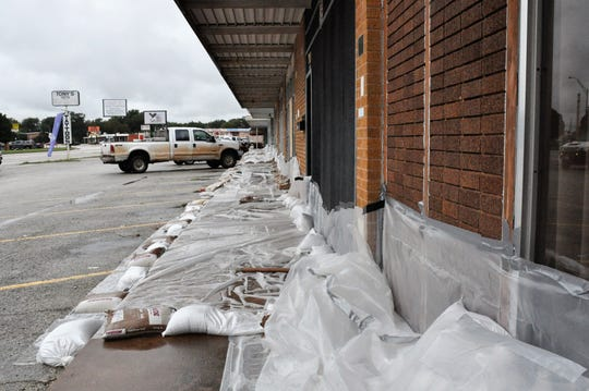 Several businesses at the Westwood Shopping Center at North Sixth and Willis streets are lined with plastic sheeting held down with sandbags to guard against flooding on Friday in case nearby Elm Creek overflows.