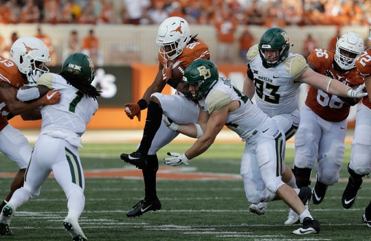 Texas running back Keaontay Ingram (26) is hit by Baylor linebacker Clay Johnston (44) during the second half Saturday, Oct. 13, 2018, in Austin.