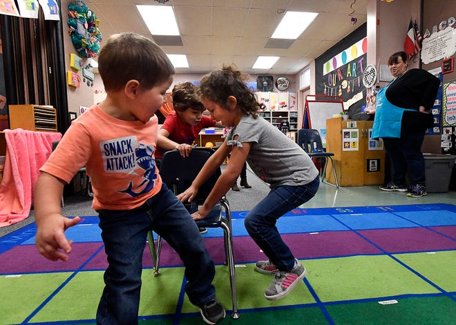 Landon Abels (left) and Liliana Vazquez scramble for the chair, while Martin Valverde (behind them) has one all to himself. At right, Natasha Thomas has turns off the CD player for the musical chairs game in the 3-year-old room at the Cedar Street Day Nursery of Abilene Friday. The facility will celebrate 25 years Monday.