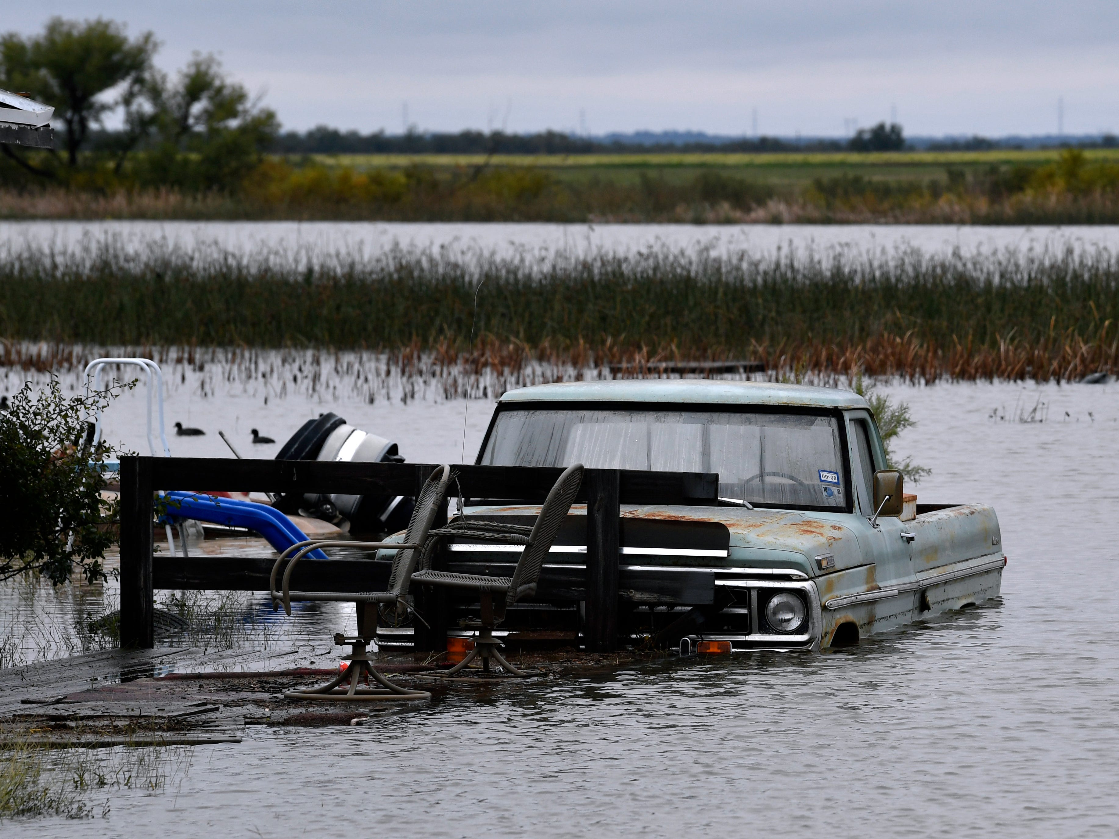 A pickup is surrounded by floodwaters Thursday Oct. 18, 2018 at Lake Stamford. Heavy rains have filled the lake to overflowing, flooding homes along the shore for the first time in several years.