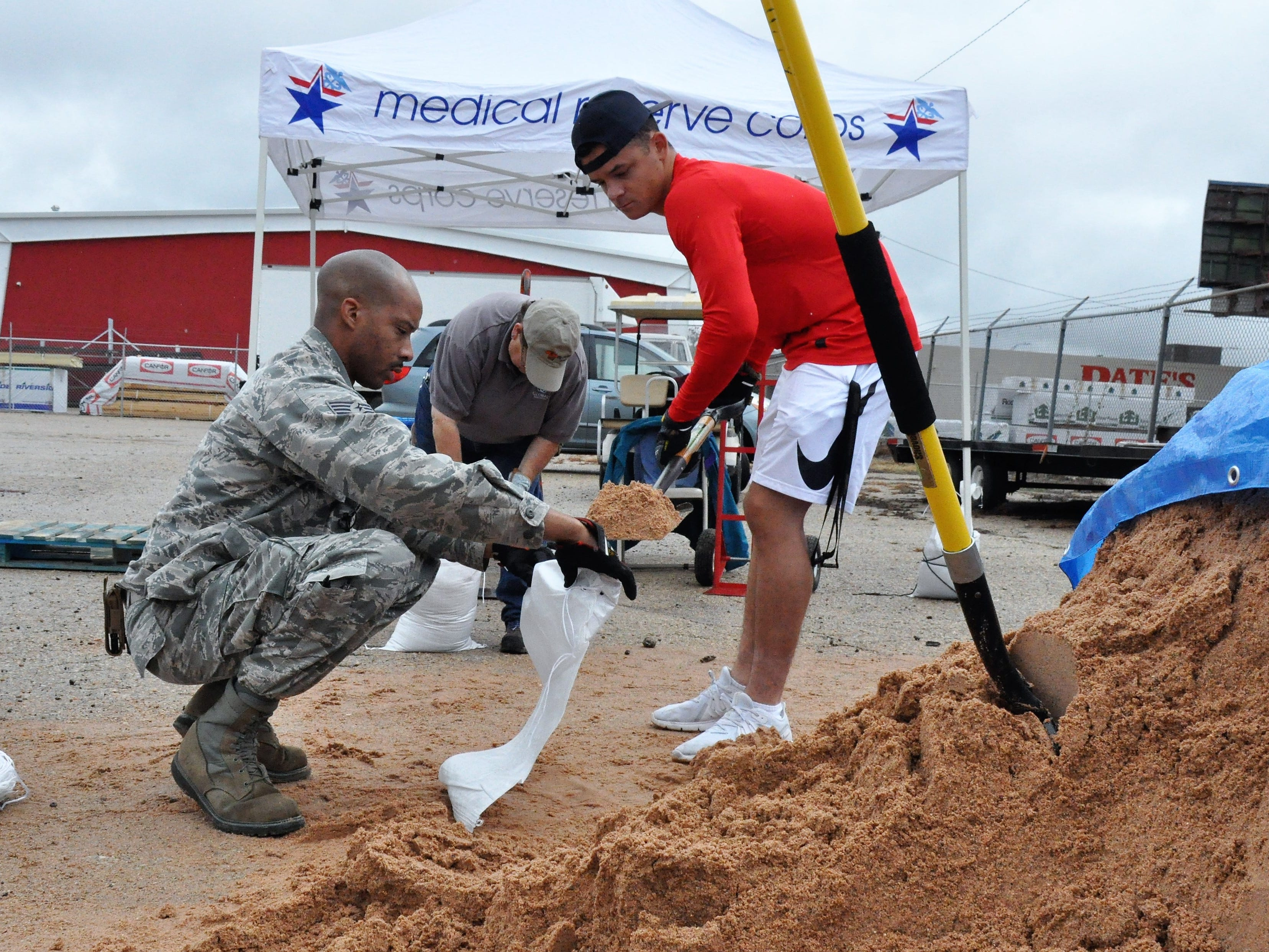 Staff Sgt. Audric Simmons, left, and Airman 1st Class Jacob Arbanas, right, from Dyess AIr Force Base help Esther Kissell, director of logistics and disaster services at Global Samaritan Resources, fill sandbags on Friday, Oct. 19, 2018.