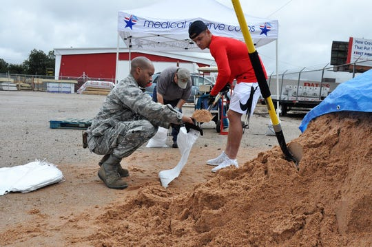 Staff Sgt. Audric Simmons, left, and Airman 1st Class Jacob Arbanas, right, from Dyess AIr Force Base help Esther Kissell, director of logistics and disaster services at Global Samaritan Resources, fill sandbags on Friday.