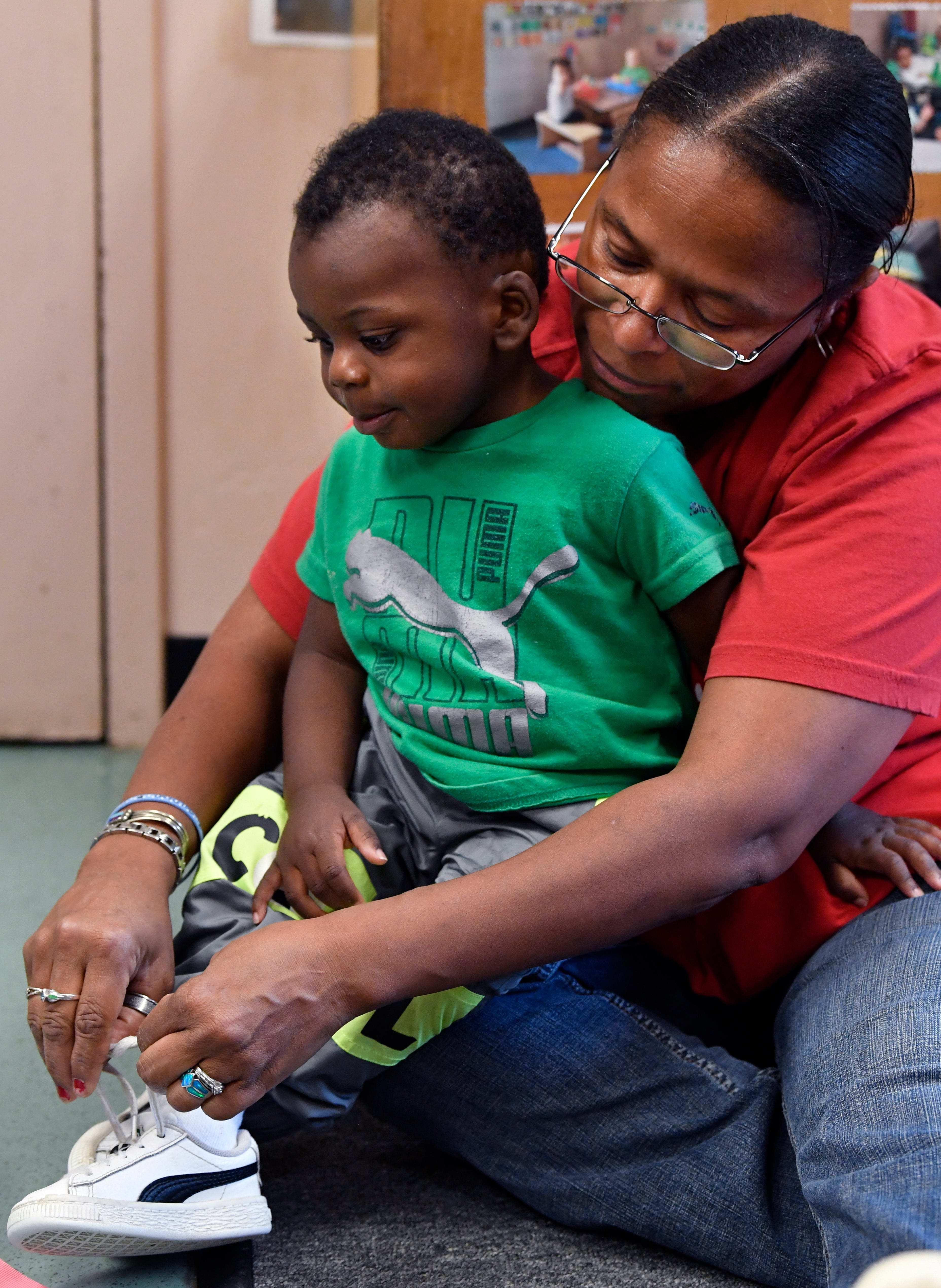 Teresa Jones helps Miles Williams put his shoe on Friday at the Day Nursery of Abilene Cedar Street Center. The day care facility will celebrate 25 years Monday.