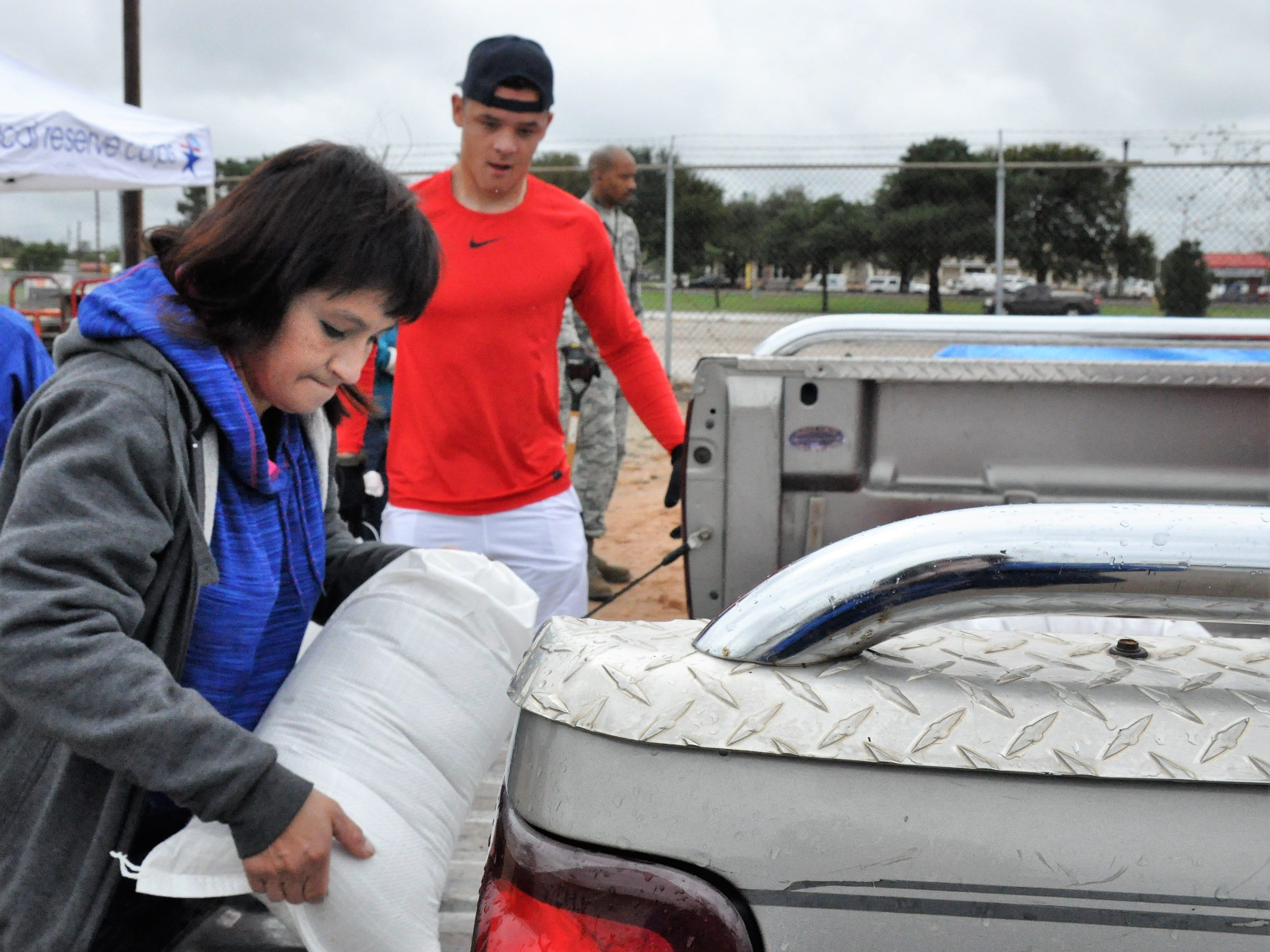 Shannon Arredondo loads into her parents' truck sandbags at Global Samaritan Resources with the help of volunteer Jacob Arbanas, airman first class stationed at Dyess AIr Force Base, on Friday, Oct. 19, 2018.