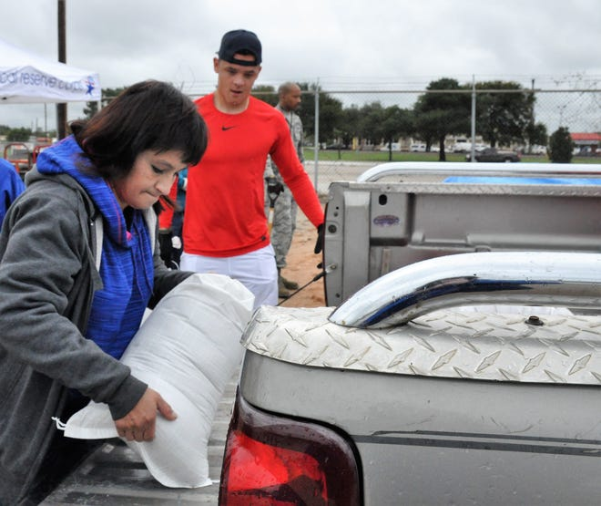 Shannon Arredondo loads into her parents' truck sandbags at Global Samaritan Resources with the help of volunteer Jacob Arbanas, airman first class stationed at Dyess AIr Force Base, on Friday.