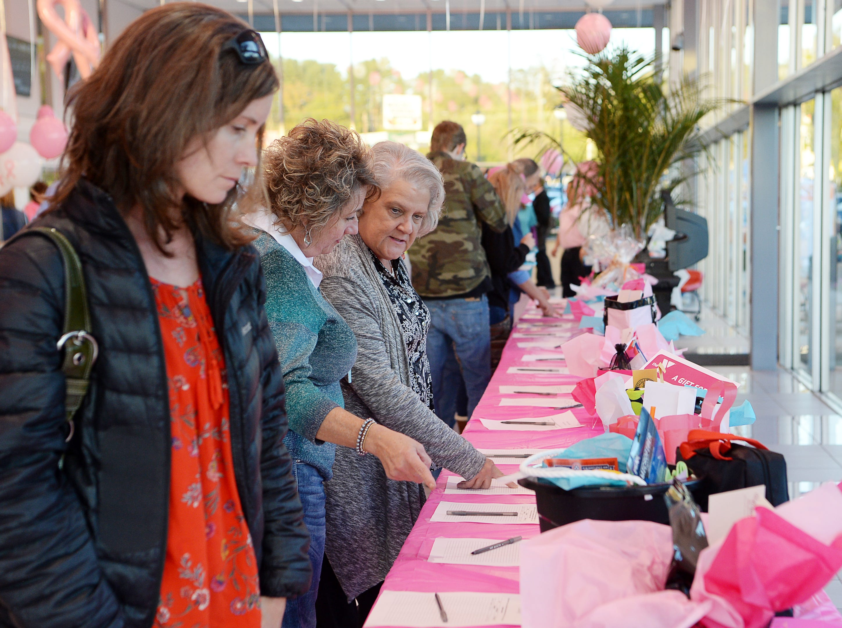 People place bids at the silent auction at the #IDrive4 breast cancer fundraiser benefitting The Hope Chest for Women at Asheville Chevrolet Oct. 18, 2018. During the month of October, the dealership is donating $5 for every #AshevilleChevyDrives4 hashtag on Instagram and Twitter.