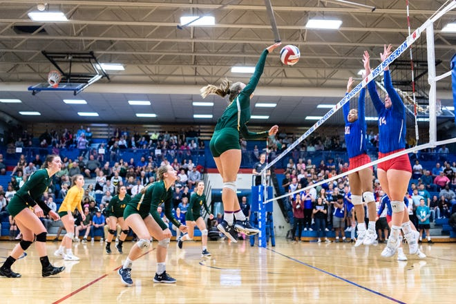 Reynolds' Grace Squires spikes the ball to West Henderson during their WMAC tournament championship volleyball game Oct. 18, 2018.