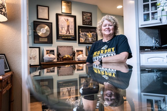 Kelly Gentry, wife of David Gentry, head coach of the Murphy high school football team, in her home in front of a wall with various awards and accolades.