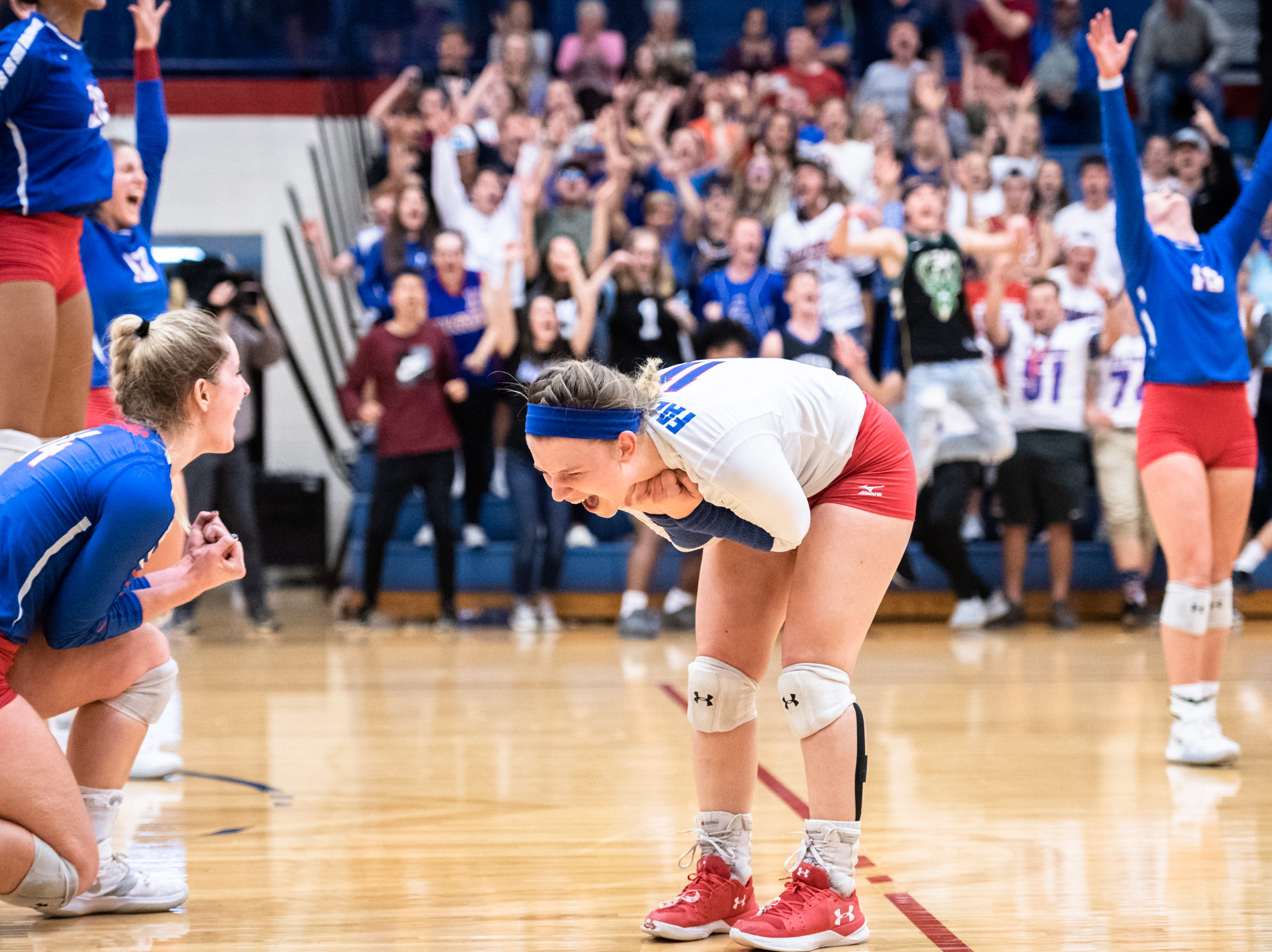West Henderson's Ashley Downer reacts to defeating Reynolds in their WMAC tournament championship volleyball game Oct. 18, 2018.