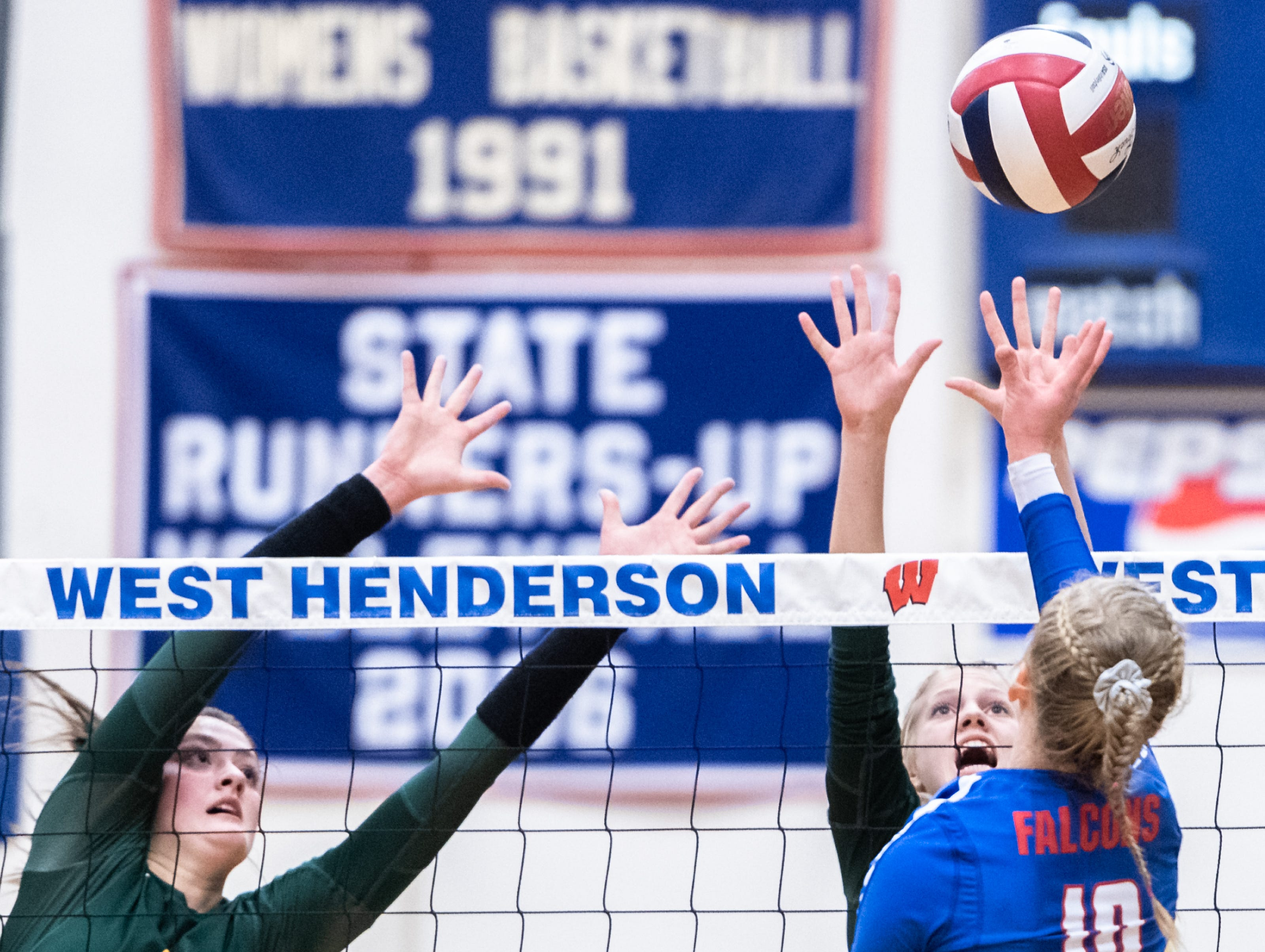 Reynolds' Delaney McCullough and Abby Hutzler attempt to block a shot by West Henderson's Malia Moore during their WMAC tournament championship volleyball game Oct. 18, 2018.